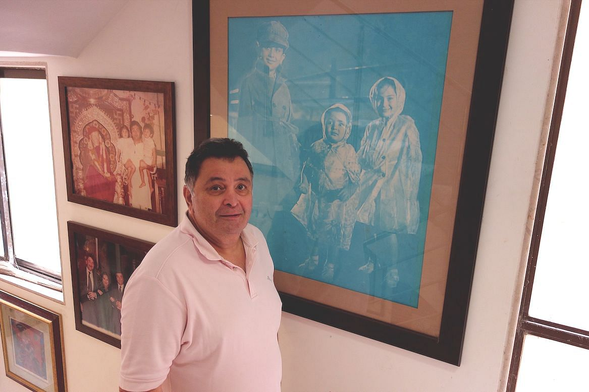 Rishi Kapoor at his residence standing beside a photo of his appearance as a child in <i>Shri 420.</i>