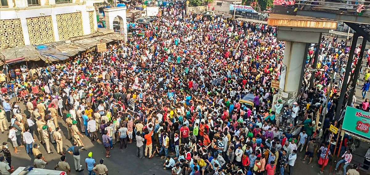 Migrant workers gather outside Bandra West Railway Station.