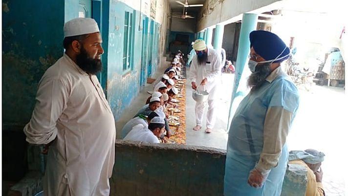 Volunteers from Gurdwara Haa Da Naara feeding Madrasa students in Malerkotla