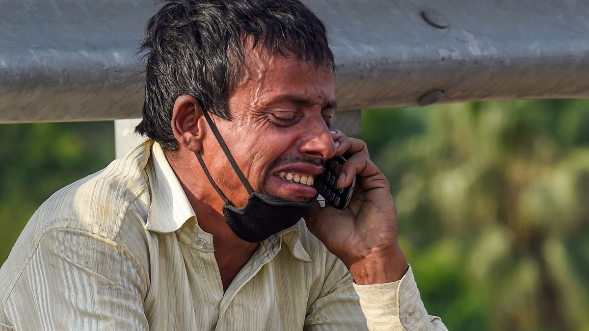 A migrant labourer reacts while talking to a relative over his mobile phone, at Nizamuddin Bridge in New Delhi, Monday.