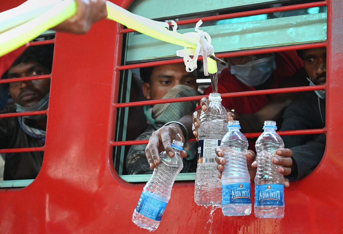 Railway employees provide water to migrants travelling in trains in Jabalpur, Thursday.