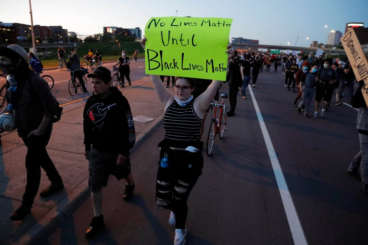 Protesters move along a highway Friday, 29 May, in Minneapolis. Protests continued following the death of George Floyd who died after being restrained by Minneapolis police officers on Memorial Day.