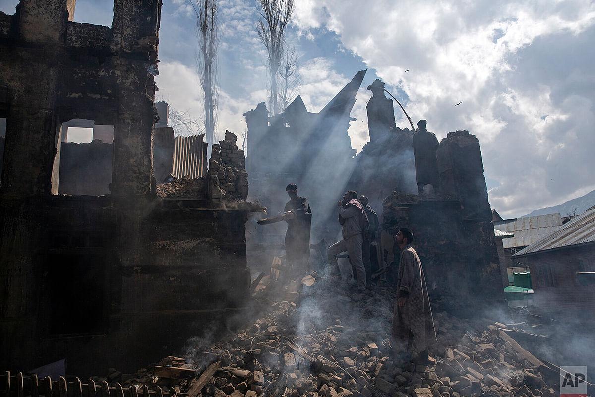 Kashmiri men dismantling a house destroyed in a gun battle in Tral village.