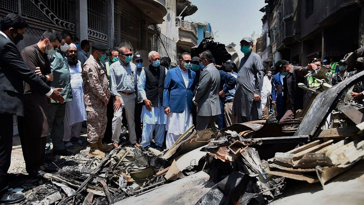 In this photo released by Pakistan Civil Aviation Authority, Provincial Governor Imran Ismail and Pakistan's Aviation Minister Ghulam Sarwar visit the site of Friday's plane crash, in Karachi, Pakistan on Saturday, 23 May.