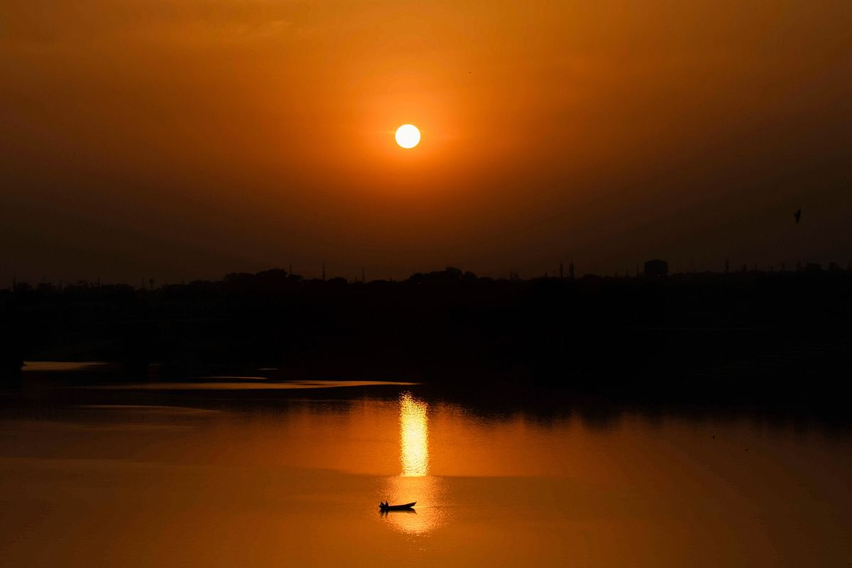 A boat is silhouetted against the setting sun as it travels across a river, in Prayagraj on Monday.