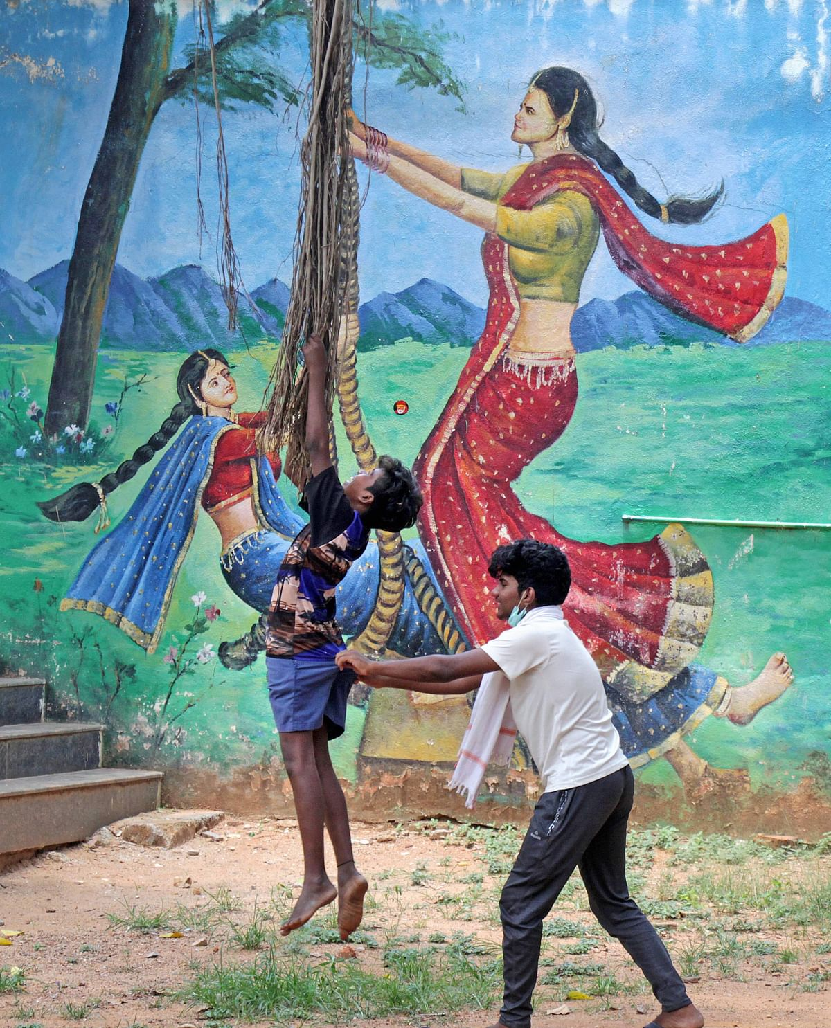 Children play in front of a mural painted on a wall, during ongoing lockdown in Bengaluru, Thursday.