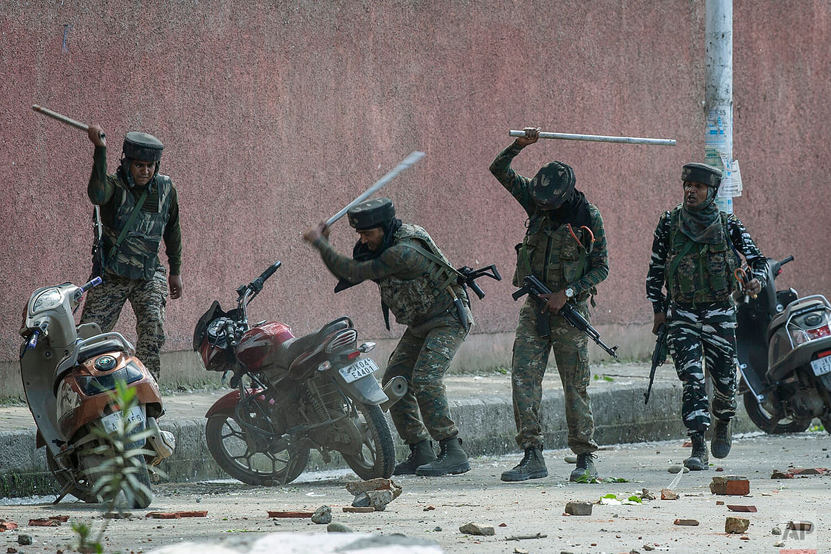 Indian paramilitary soldiers break motorbikes parked outside a college as they clash with students protesting in Srinagar against the rape of a 3-year-old child.