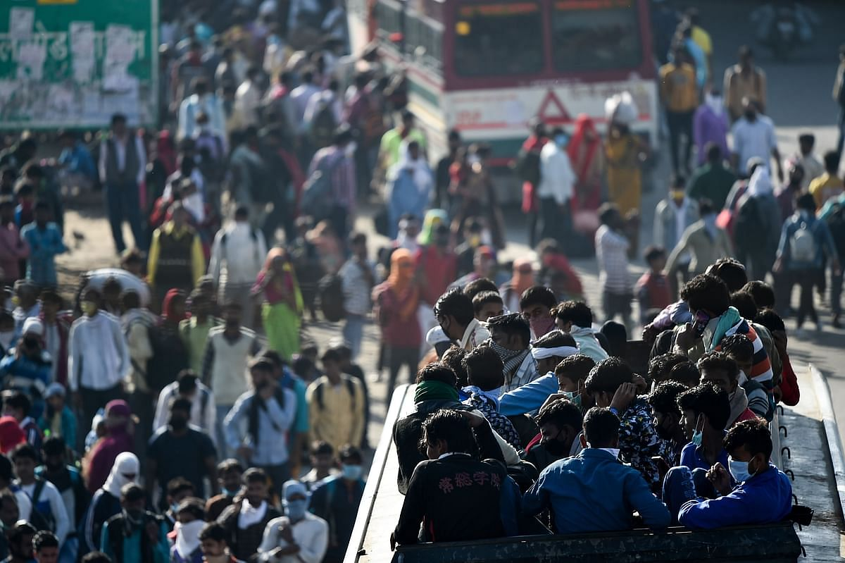 Migrants board a crowded bus to their native village, during a nationwide lockdown imposed in the wake of coronavirus pandemic, in Ghaziabad, Saturday, 28 March 2020.