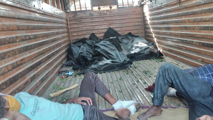 Bodies wrapped in tarpaulin sheets can be seen dumped in the corner of a truck and injured migrant workers lay right next to them.