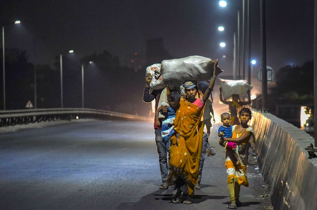A migrant family from Madhya Pradesh walks along a road to reach home in Navi Mumbai, late Sunday night.