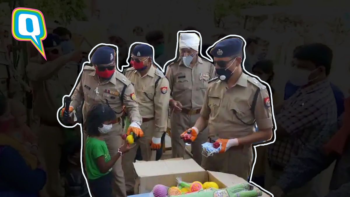 Jhansi Police officers distributing masks and toys to migrant children.