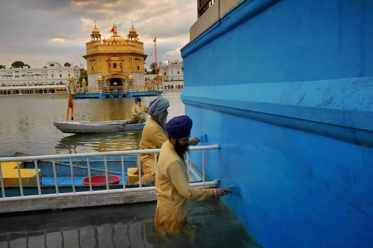 Sikh Sewadars (volunteers) paint the boundary of the Sarovar of Harmandir Sahib, also known as Golden Temple in Amritsar, Thursday.