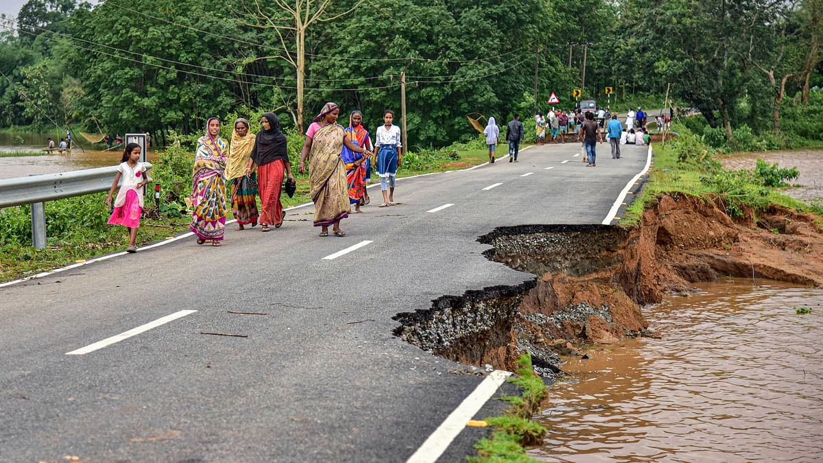 Villagers walk on a road that is partially damaged and washed away due to floods following heavy rainfall, in Goalpara district of Assam on Monday, 25 May.