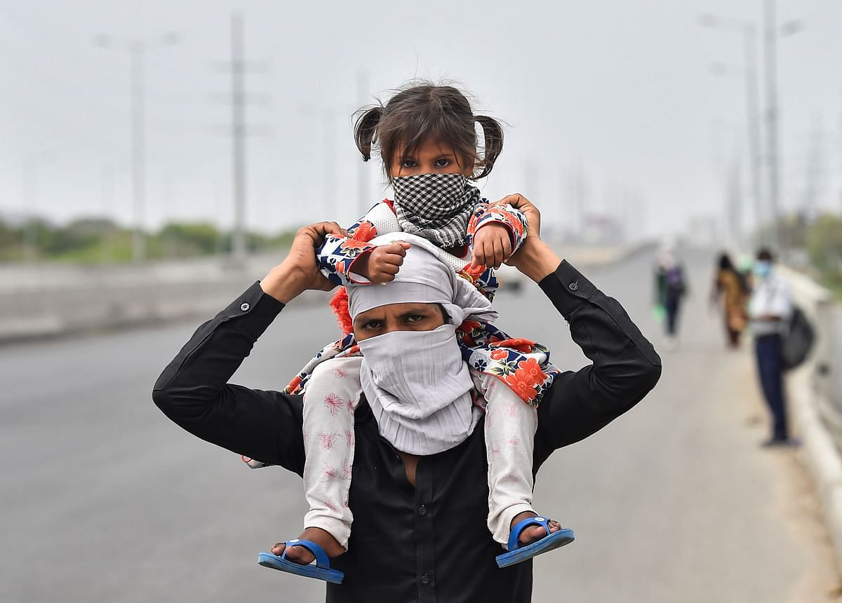 A worker with a child on his shoulder walks to his village amid a nationwide complete lockdown, on the NH24 near Delhi-UP Border in Ghaziabad, Thursday, 26 March 2020.