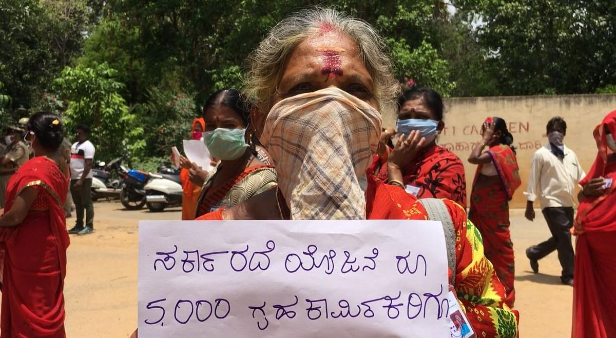 Dhanalaskhmi, 65 years old. Her poster reads: ''Include Domestic Workers, Pay Us Rs 5,00 Too""