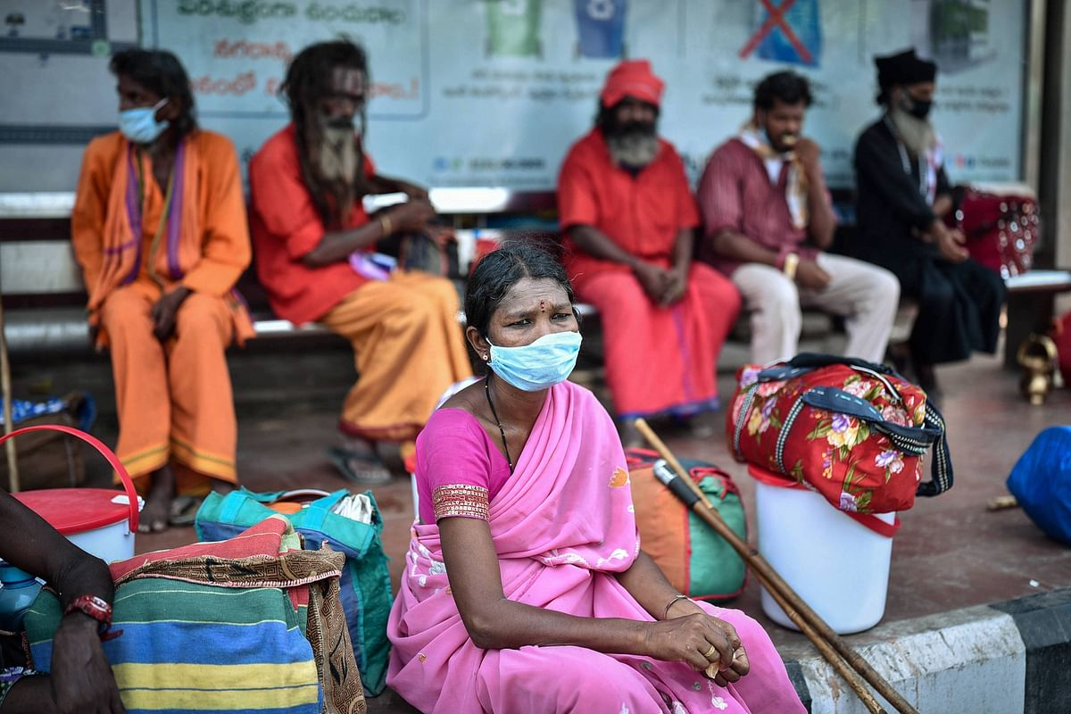 A woman waits at a bus stop to return to her native place in Vizianagaram after leaving a quarantine facility,  in Vijayawada, Tuesday.