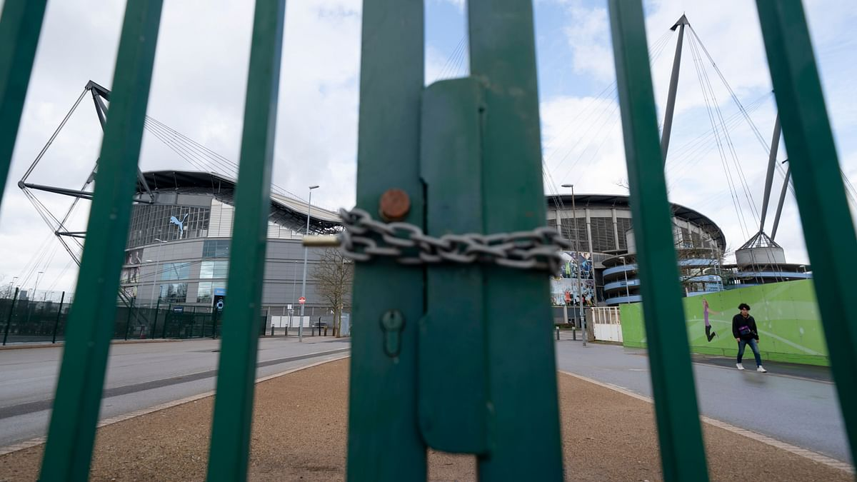 A locked gate is seen by the Etihad Stadium where Manchester City was due to play Burnley in an English Premier League match Saturday March 14, 2020.