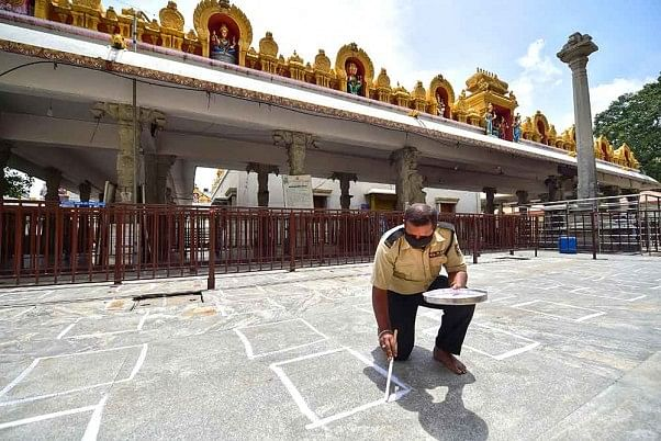 A worker draws social distancing markers at a temple ahead of its reopening.