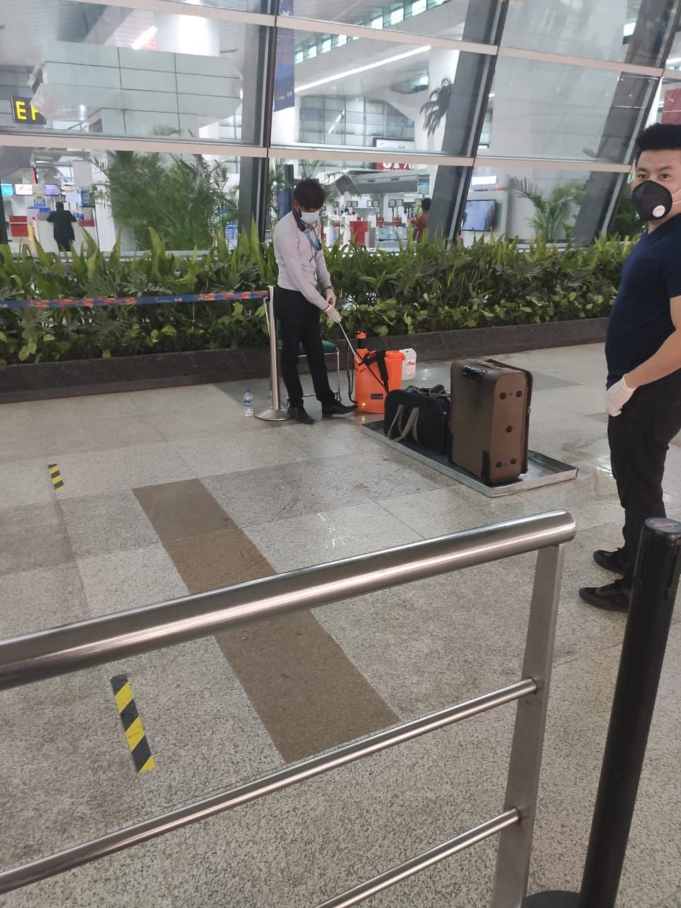 The airport staff were spraying disinfectants on the luggage at the Delhi airport.