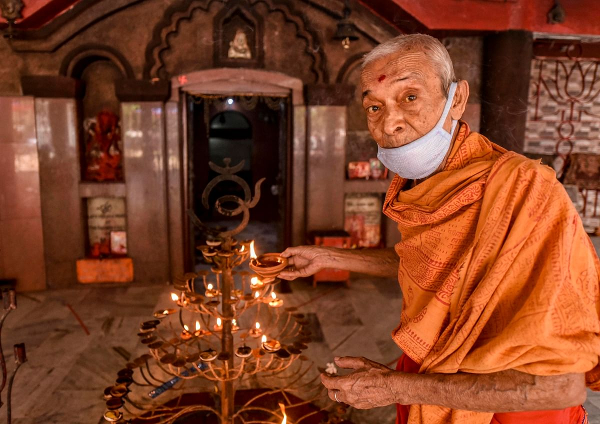 A priest offers prayers at Ugratara temple after the authorities permitted opening of all religious places with certain restrictions, during the fifth phase of the ongoing COVID-19 lockdown, in Guwahati.