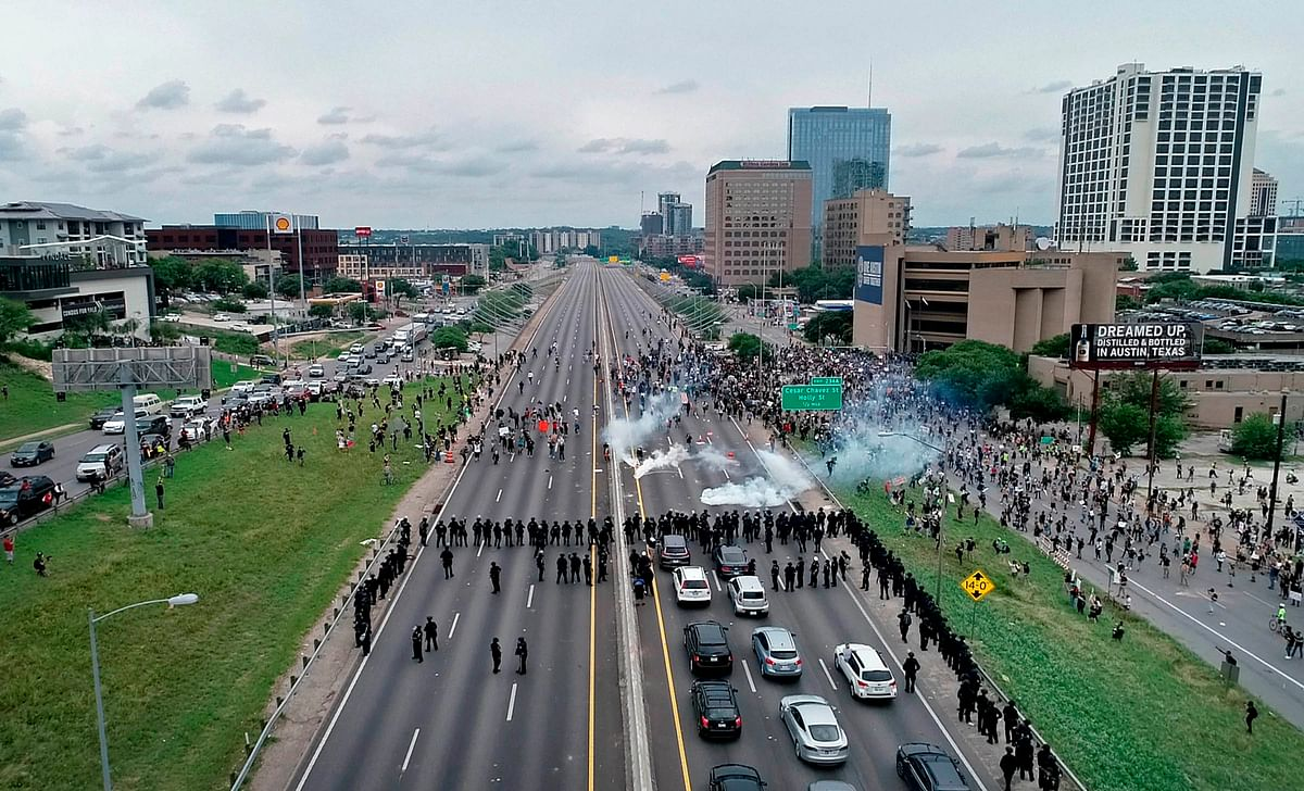 Police use tear gas to clear away protesters who blocked Interstate 35 near the Austin Police Department headquarters Sunday, 31 May, in Austin, Texas, during demonstrations over the death of George Floyd.