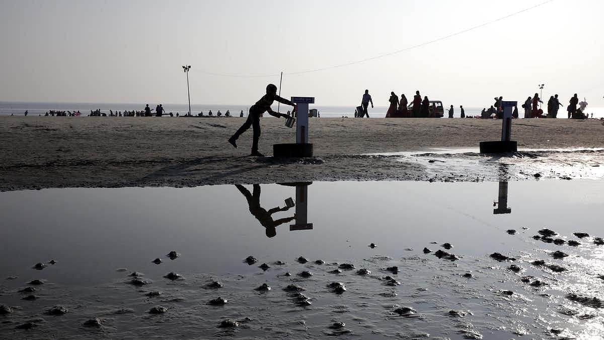 An Indian boy collects drinking water from a tap on the bank of Bay of Bengal