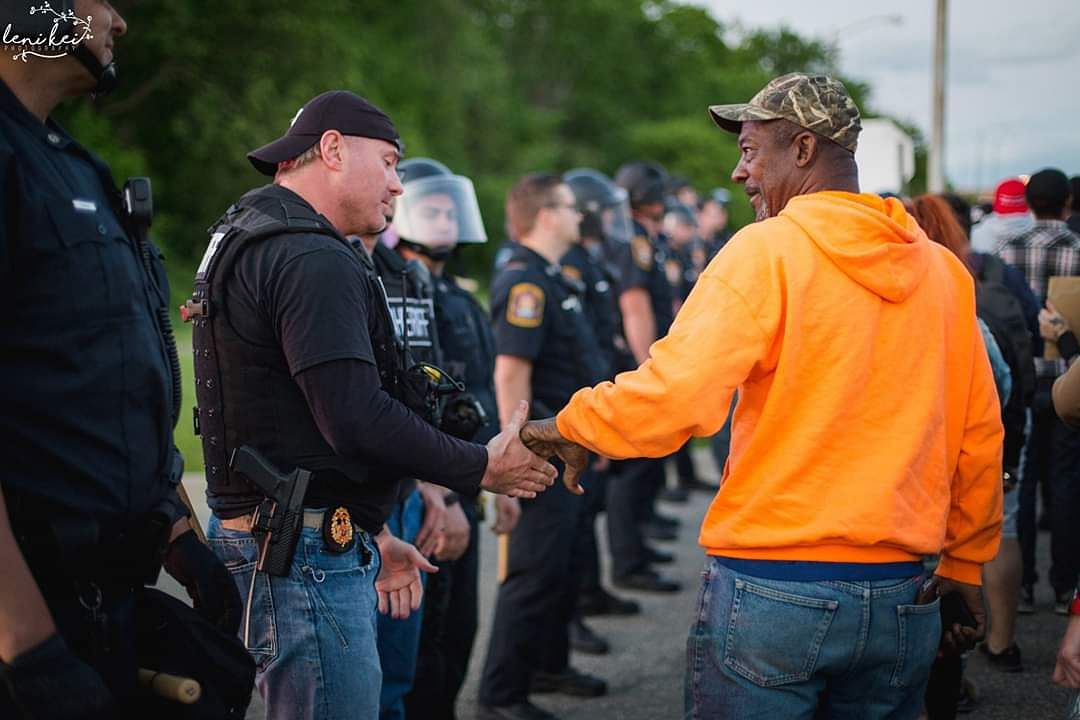 Policemen stand in solidarity with protesters in US.