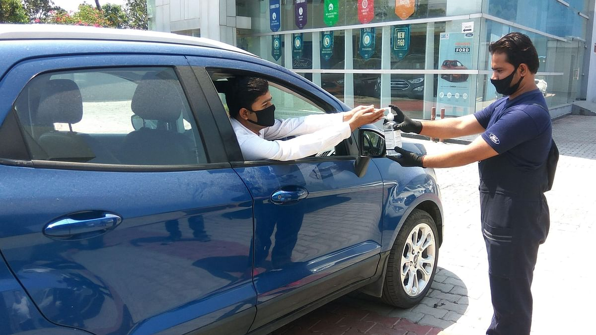 A customer taking a test drive at a Ford showroom sanitises his hands at the entrance.