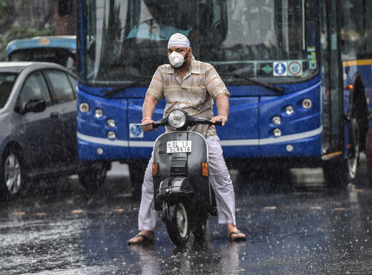 A scooterist stuck in traffic during pre-Monsoon rainfall, in New Delhi, Wednesday, 24 June.