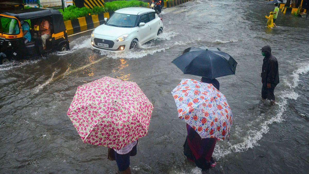 Commuters wait to cross a waterlogged street as vehicles ply, during heavy rainfall, at Vashi in Navi Mumbai, Sunday, July 5, 2020.