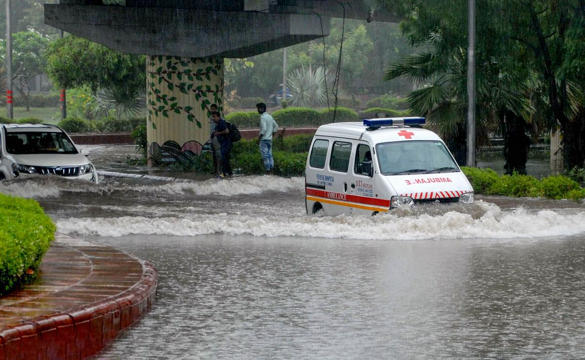 An ambulance wades through a waterlogged road after heavy rains, in Noida.