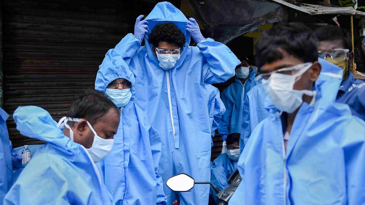 Health workers wear PPE kits before conducting medical check-up of residents of Kurar village, at Malad (East) in Mumbai on 13 July.