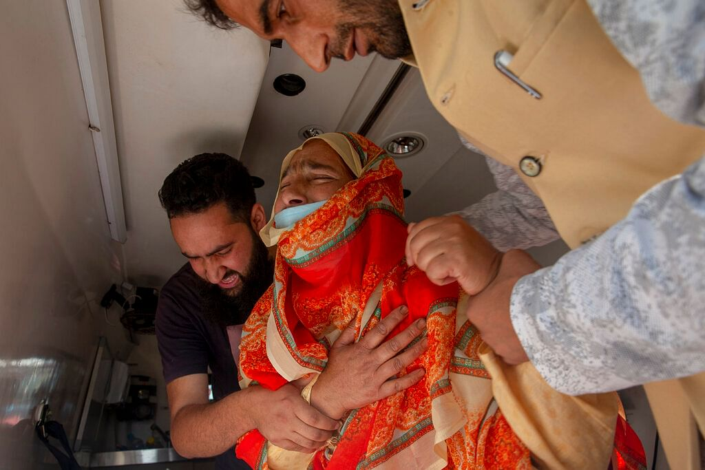 A relative of politician Sheikh Wasim Bari is comforted by others inside an ambulance in Bandipora town, north of Srinagar, Thursday, July 9, 2020.