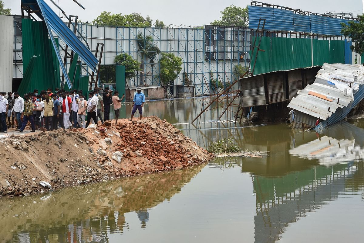 Locals look on at the site of a building collapse, due to monsoon rain, at Anna Nagar in New Delhi.