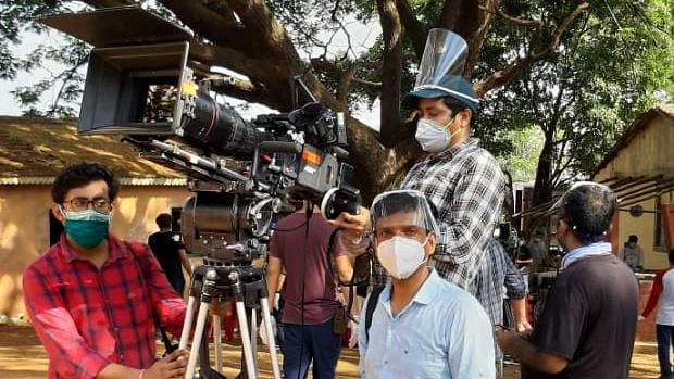 The cast and crew wear masks while shooting for an ad.