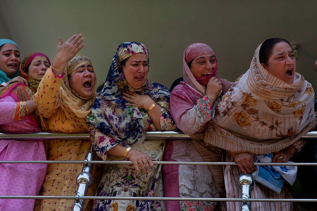 Relatives of Kashmiri civilian Bashir Ahmed Khan grieve as they watch his funeral on the outskirts of Srinagar, Wednesday, July 1, 2020.