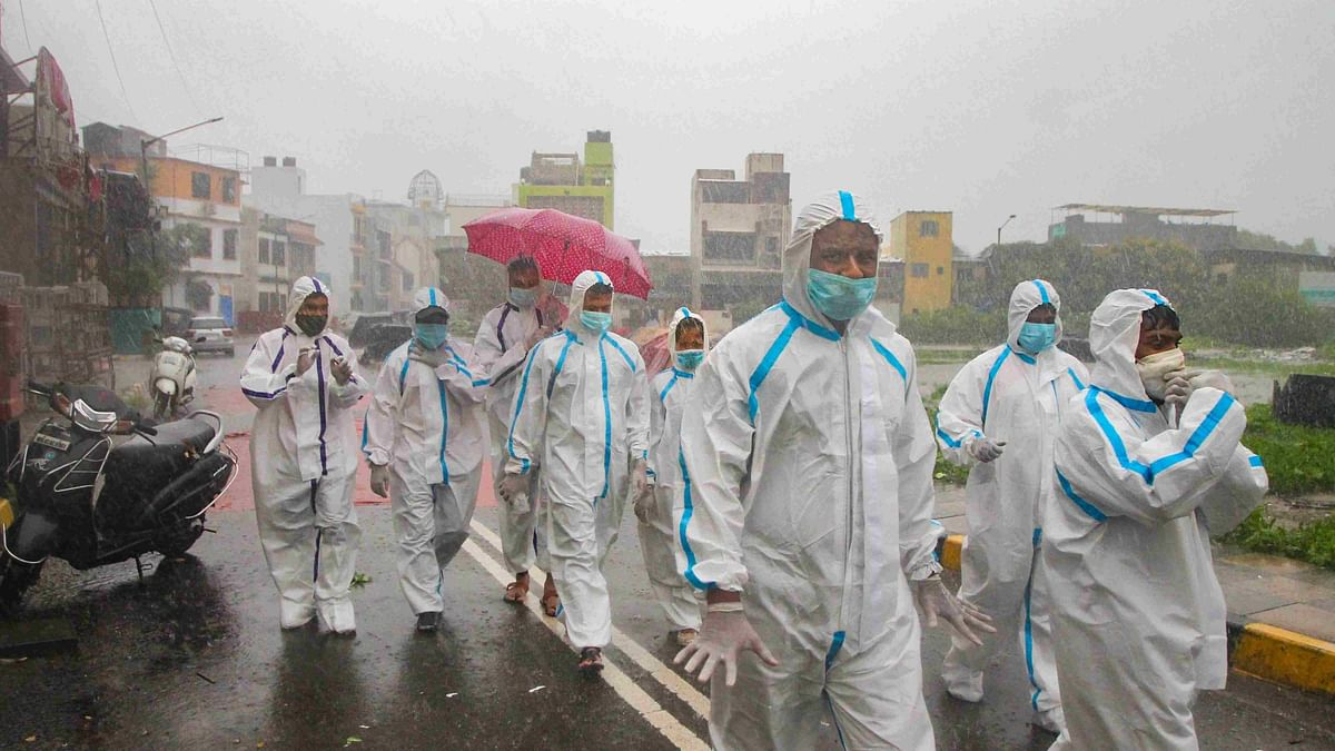 Health workers wearing PPE arrive for COVID-19 medical checkup at a containment zone during heavy rain at Malad in Mumbai.