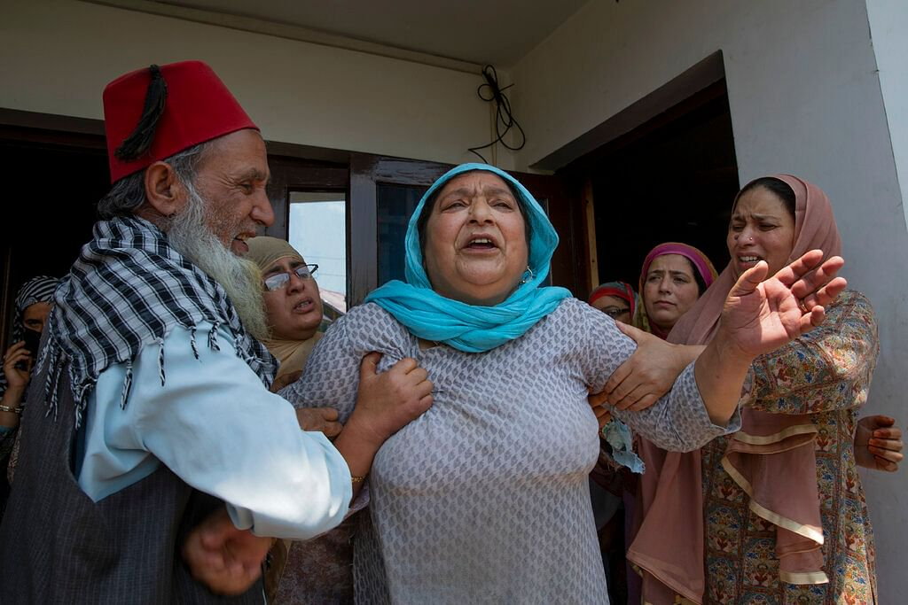 Relatives comfort the wife of civilian Bashir Ahmed Khan at their residence on the outskirts of Srinagar, Wednesday, July 1, 2020.