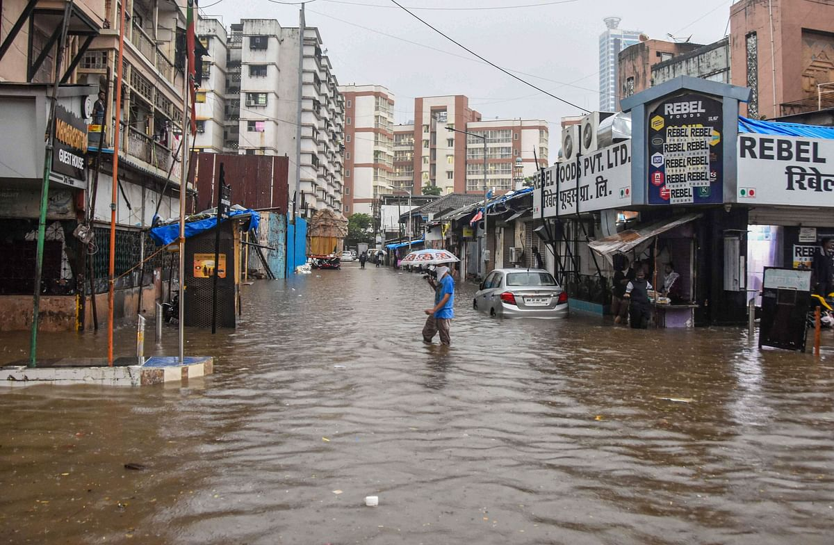 A commuter crosses a water-logged street in Parel, Mumbai.