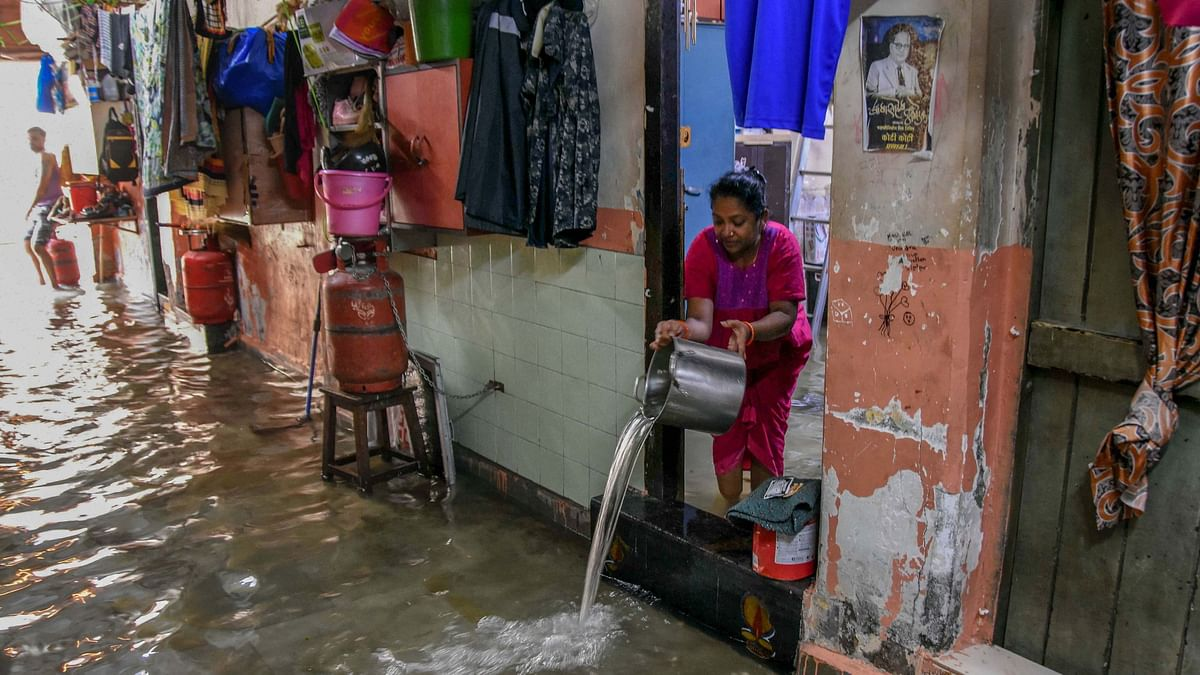 A woman drains water from her house in Parel, Mumbai.