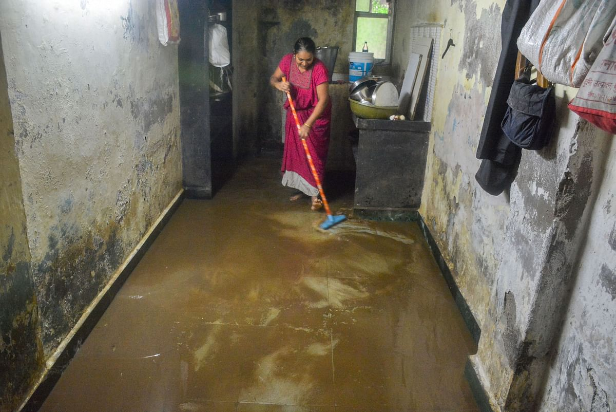A woman tries to clean the muck in her house that entered after her house got flooded in Parel.
