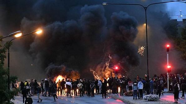 Smoke billows from burning tyres and pallets and fireworks as a few hundred protesters gather in the Rosengard neighbourhood of Malmo, Sweden.<b></b>