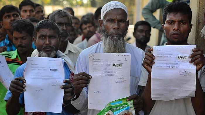People show their acknowledgement receipts after checking their names in a draft for National Register of Citizens (NRC), in Guwahati in January 2018.