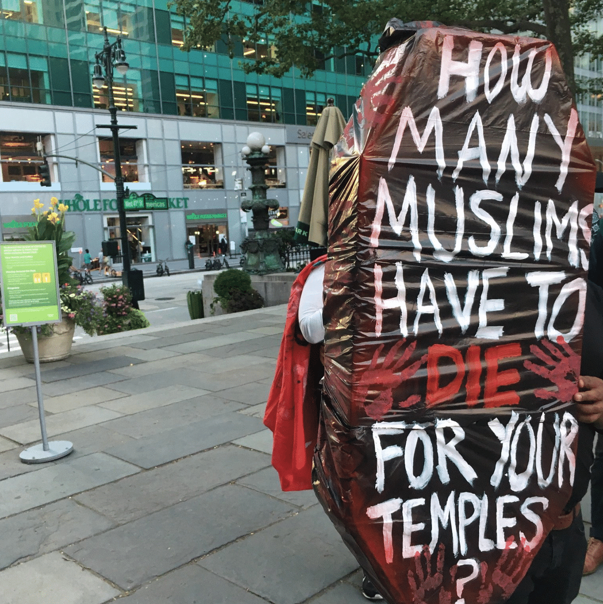 """Image from the protest against the Ram Mandir billboard in NYC of a coffin asking the question """"How many Muslims have to die for your temples?"""""""