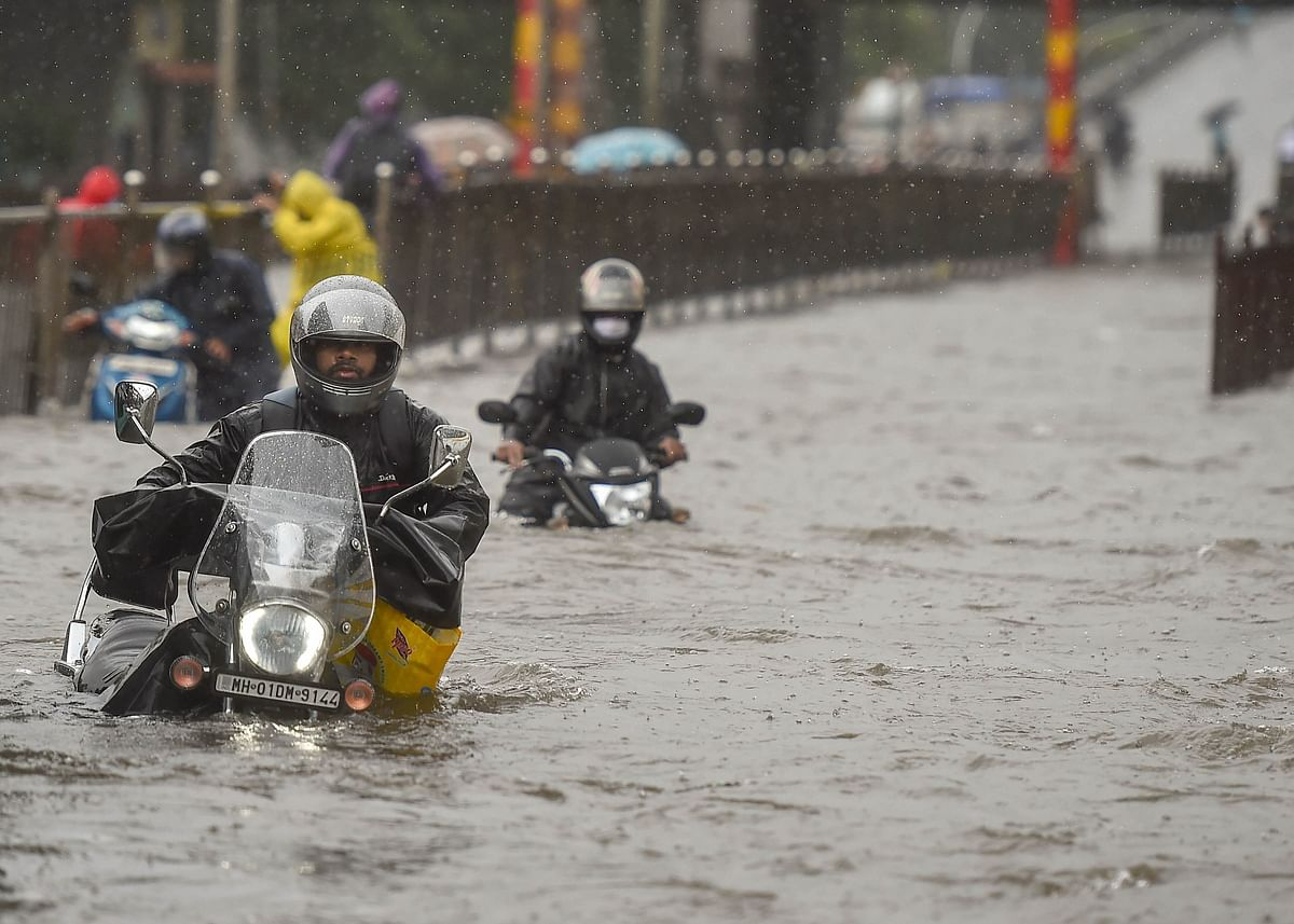 Commuters wade through a waterlogged street in Sion.