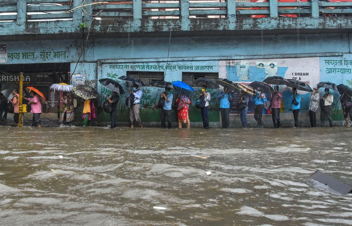 Pedestrians try to cross a waterlogged street in Byculla.