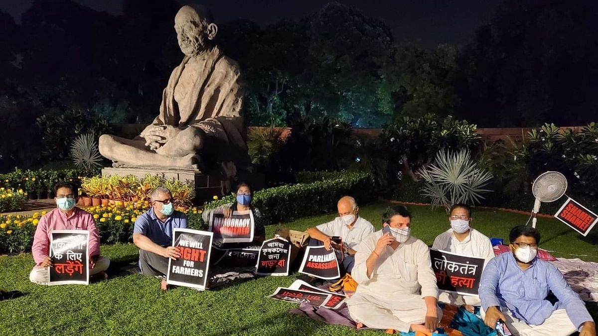 Singing, sitting on grass, eight suspended Rajya Sabha members have been camping near the Gandhi statue.