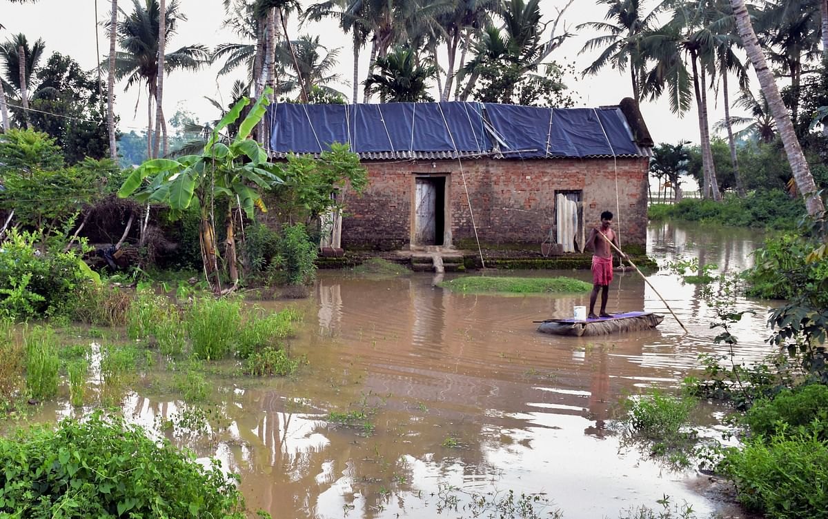 A villager rows a boat in a flooded area following overflowing of Bhargabi river, in Puri district.