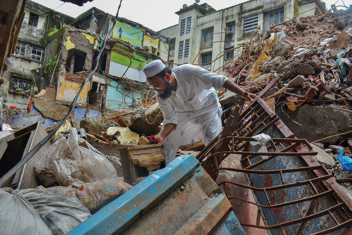 A resident looks for some households amid the debris at the building collapse site after completion of rescue works by NDRF and Fire Brigade personnel, at Bhiwandi in Thane, Thursday, 24 September.
