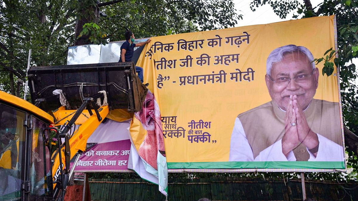 Workers remove a hoarding of Bihar CM Nitish Kumar as per model code of conduct following announcement of Bihar Assembly Election dates, in Patna, Friday, 25 September 2020.